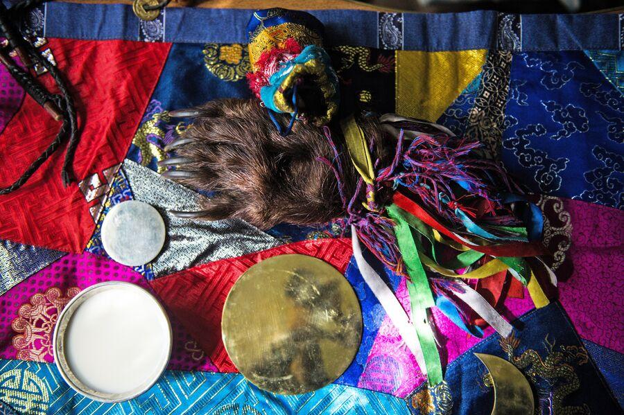 Предметы, используемые шаманом во время проведения обрядов. Одним из главных атрибутов шамана является зеркало – кузунгу. С его помощью шаман проводит камлания, занимается лечением и гаданием.  Медвежья лапа может использоваться, как колотушка для бубна. Тувинские шаманы в своих обрядах часто обращаются к духу медведя