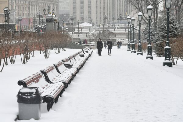 Прохлжие в Александровском саду во время снегопада в Москве