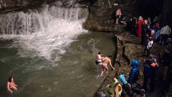 Верующие во время традиционного праздничного купания в Крещенский сочельник в водопадах реки Жане у города Геленджик в Краснодарском крае