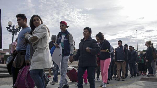 Мигранты из Центральной Америки, ищущие убежища в США, на границе Мексики и США в Тихуане