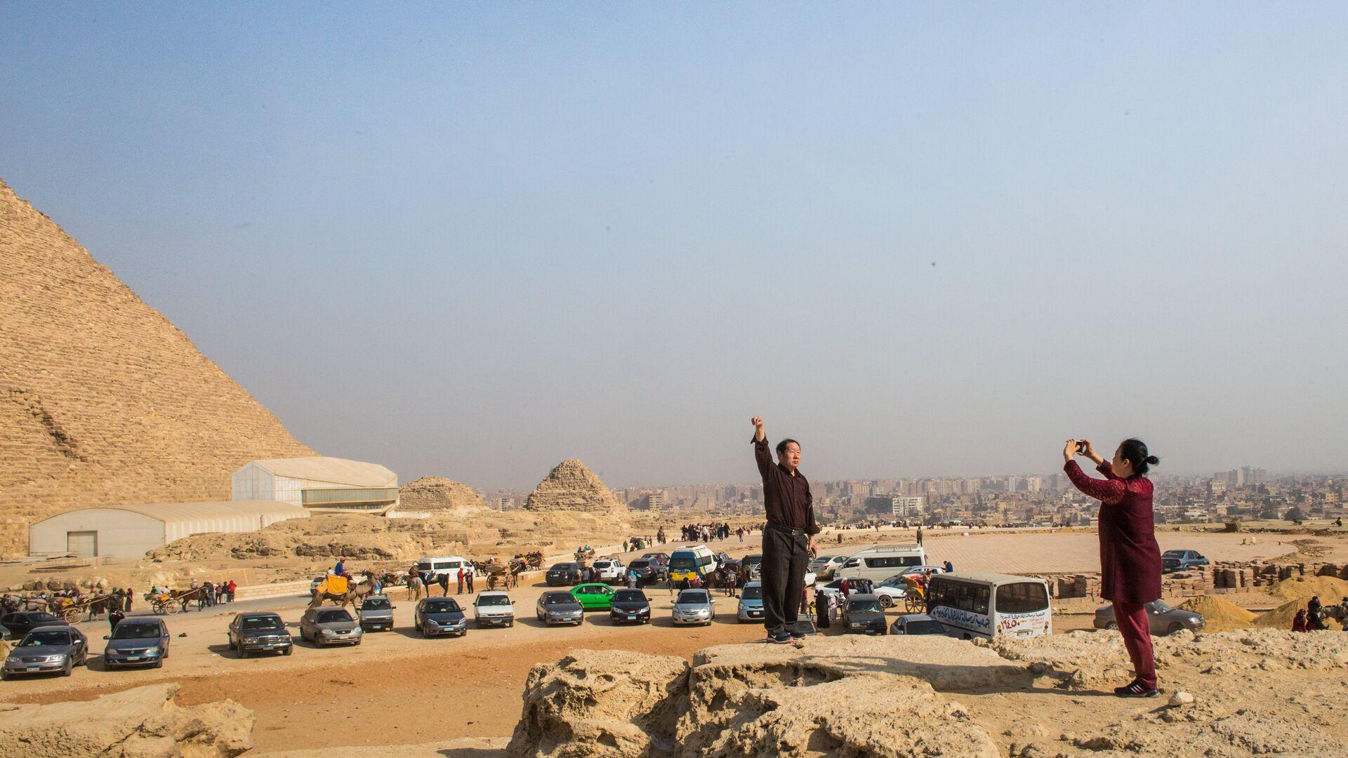 Туристы фотографируются на фоне древнеегипетских пирамид в Эль-Гизе, пригороде Каира - РИА Новости, 1920, 29.06.2021