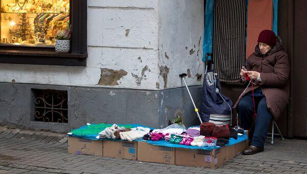Женщина продает вязаные вещи в старом городе в Вильнюсе