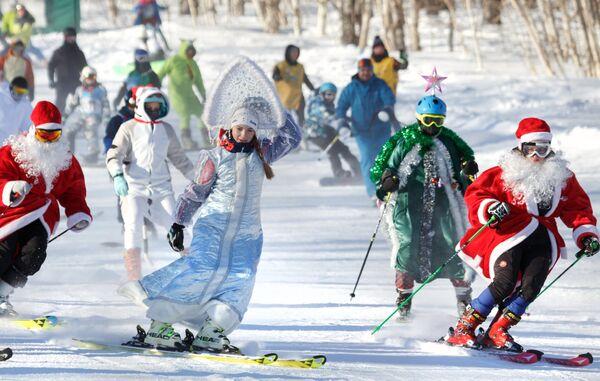 Участники массового спуска в карнавальных костюмах с горы Морозной на фестивале снега и зимних видов спорта Морозная FEST в Камчатском крае