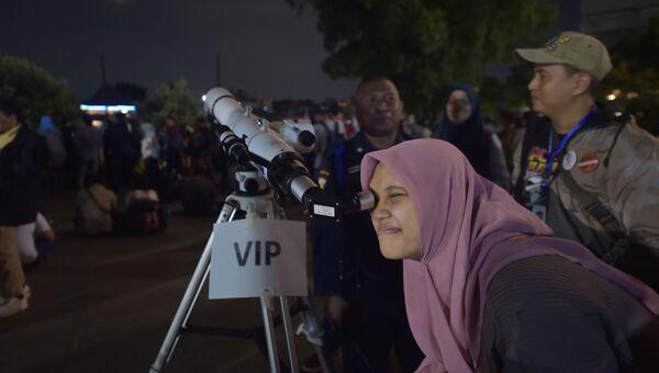 Женщина наблюдает суперлуние в Индонезии