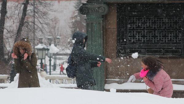 Молодые люди играют в снежки на Манежной площади в Москве. Архивное фото