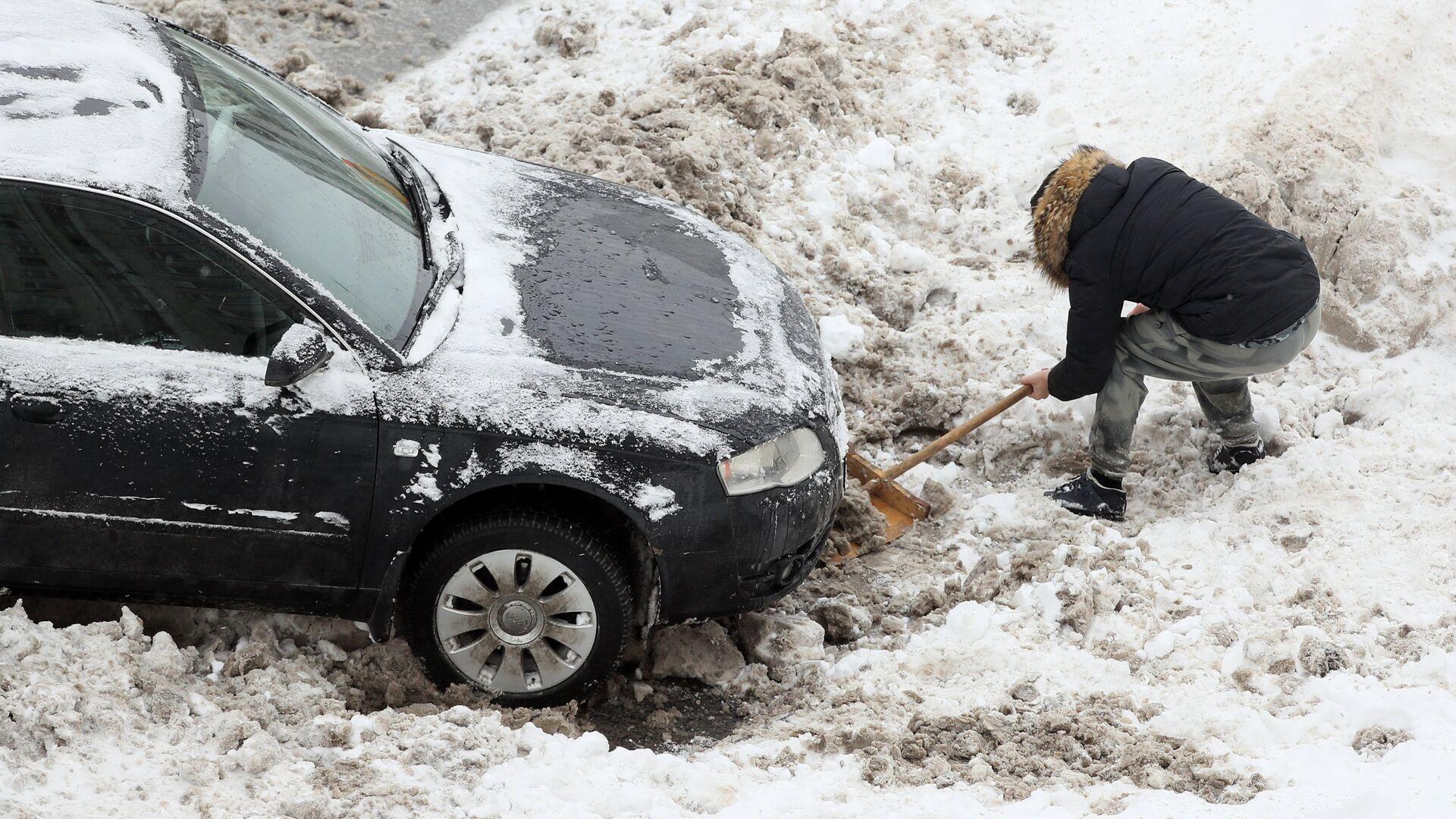 Водитель откапывает из снега свою машину после снегопада - РИА Новости, 1920, 17.01.2021