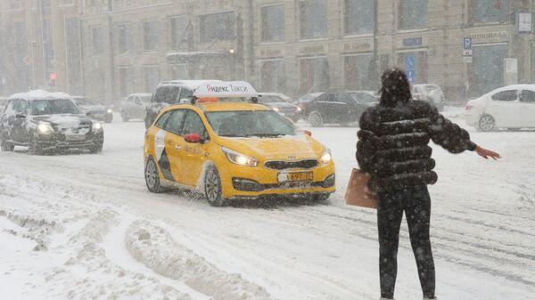 Девушка ловит такси на Тверской улице во время снегопада. 4 февраля 2018