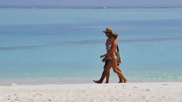 Пара гуляет по пляжу на одном из Мальдивских островов