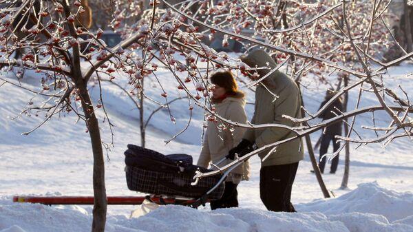 Семья с ребенком гуляет в парке