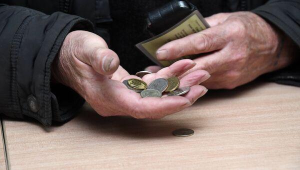 Мужчина держит монеты в руке. Архивное фото