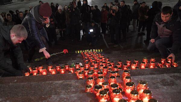 Люди зажигают свечи и кладут цветы на ступени Храма Христа Спасителя во время акции памяти о жертвах крушения самолета Ан-148 Саратовских авиалиний