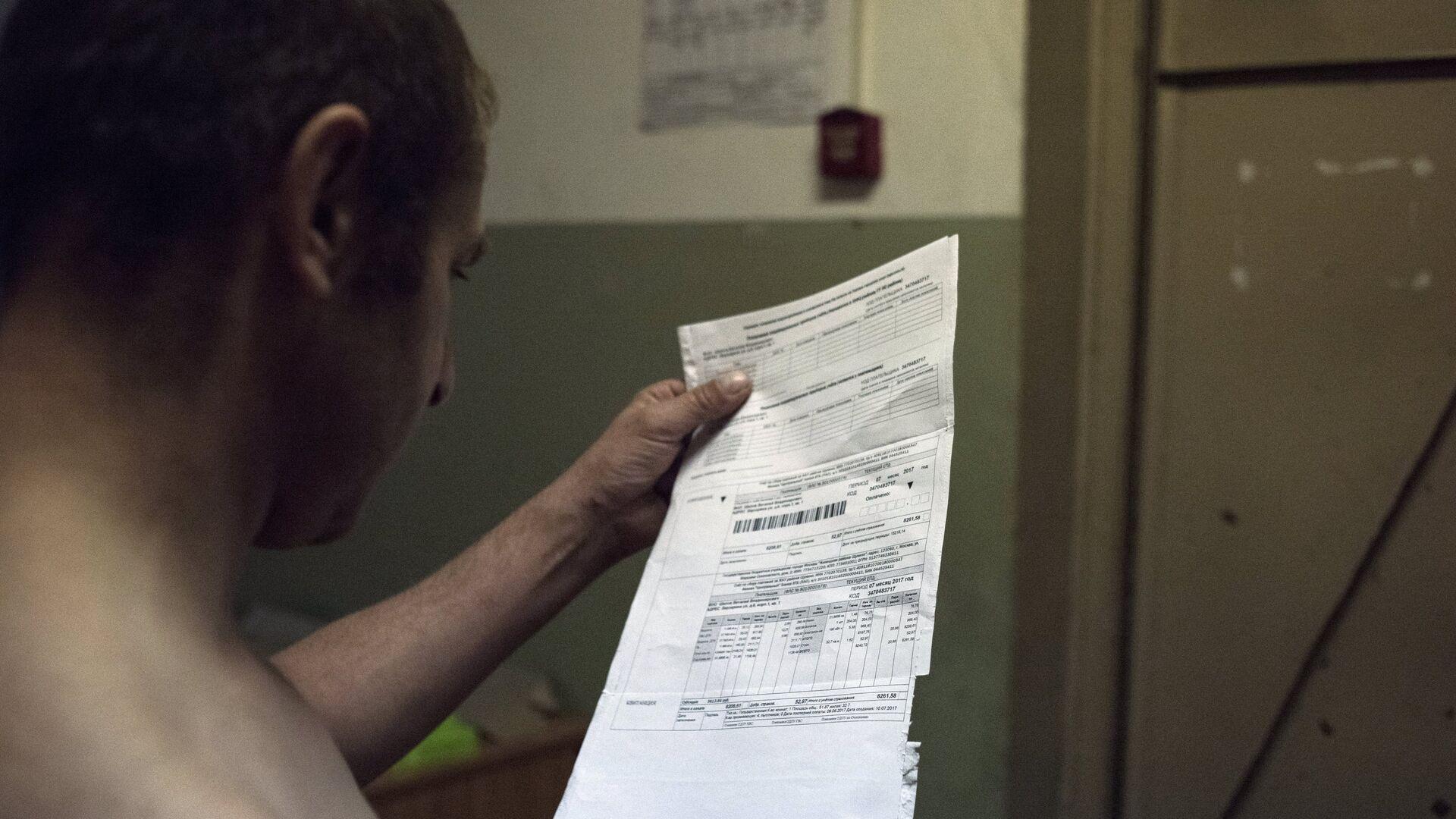 Мужчина держит квитанцию оплаты коммунальных услуг - РИА Новости, 1920, 14.09.2020