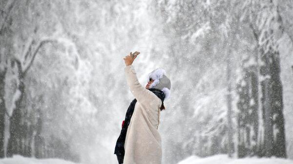 Девушка фотографируется во время снегопада