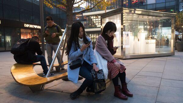 Горожане на территории многофункционального комплекса Sanlitun Soho в Пекине