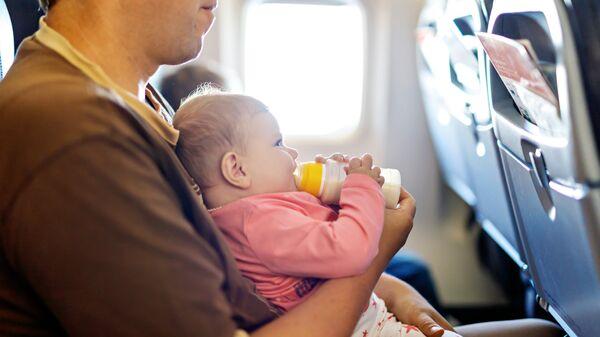 Мужчина с грудным ребенком в салоне самолета. Архивное фото