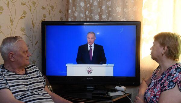 Мужчина с женщиной смотрят трансляцию ежегодного послания президента РФ Владимира Путина к Федеральному собранию. 1 марта 2018