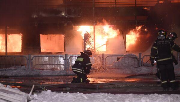 Сотрудники пожарной службы МЧС России во время тушения пожара на прогулочном теплоходе на Нагатинской набережной в Москве.