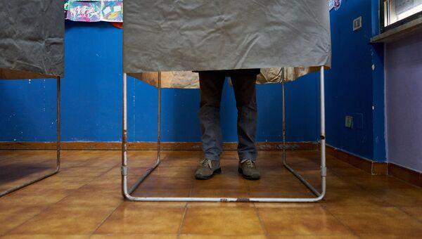 Избиратель в кабинке для голосования. Архивное фото