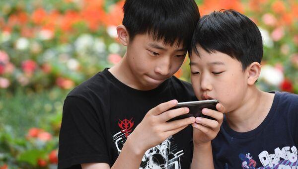 Дети играют с мобильным телефоном