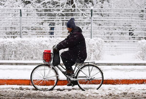 Мужчина едет на велосипеде во время снегопада в городе Шэньян, Китай