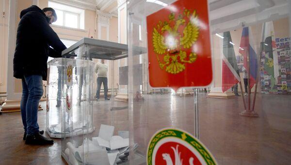 Мужчина опускает бюллетень в урну во время голосования на выборах президента Российской Федерации на избирательном участке №42 в Казани. 18 марта 2018