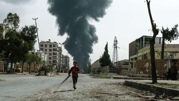 Мальчик бежит по улице в городе Дума, Сирия. Архивное фото