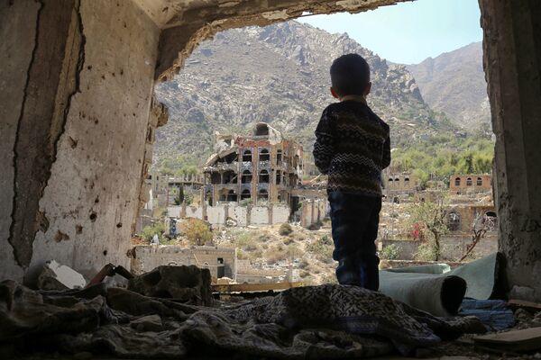 Ребенок в разрушенных после авиаудара зданиях в городе Таиз, Йемен