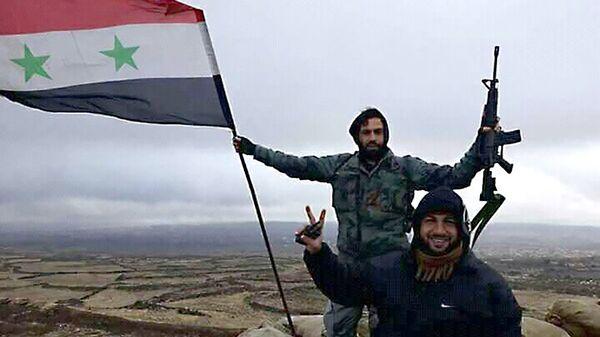 Солдаты сирийской армии с флагом Сирии. Архивное фото