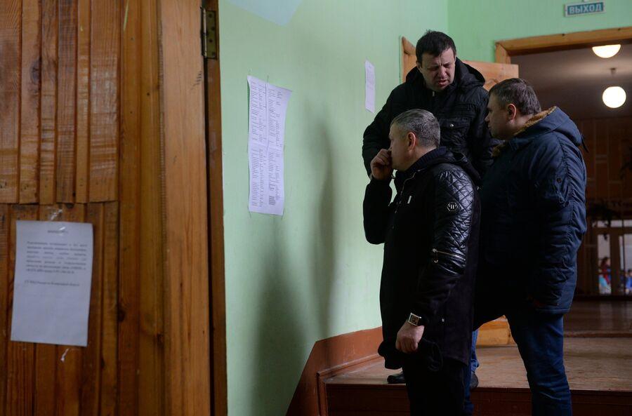 Люди смотрят списки пропавших без вести при пожаре в торговом центре Зимняя вишня в Кемерово. 26 марта 2018