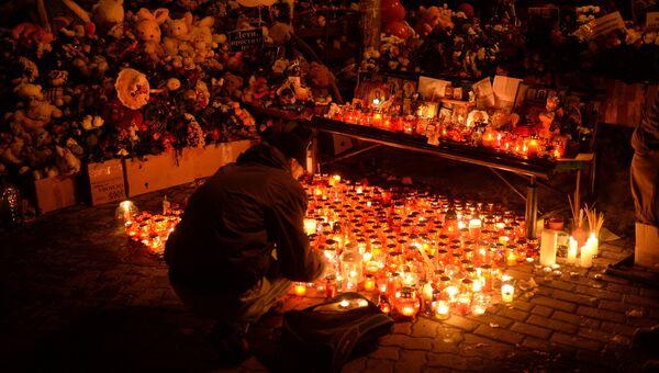 Зажженные свечи возле здания торгового центра Зимняя вишня в Кемерово, где произошел пожар. 26 марта 2018