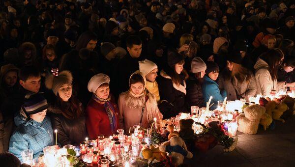 Участники акции зажигают свечи в память в память о погибших при пожаре в кемеровском торговом центре Зимняя вишня. Архивное фото