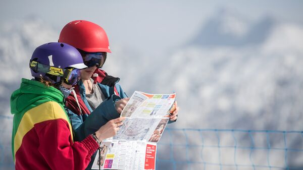 Отдыхающие на вершине Роза Пик рассматривают карту горного курорта Роза хутор в Красной поляне