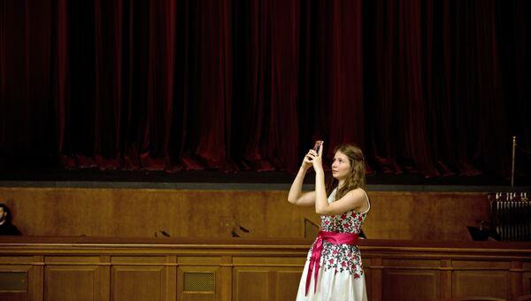 Зрительница делает фотографию в зрительном зале Новосибирского оперного театра перед началом спектакля.
