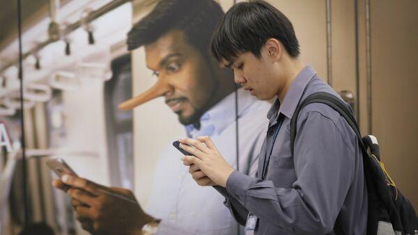 Молодой человек проходит мимо рекламы, запрещающей распространение фейковых новостей на вокзале в Куала-Лумпур, Малайзия