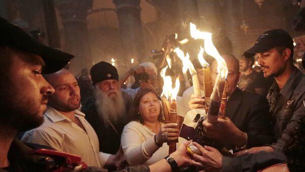 Верующие со свечами, зажженными от Благодатного огня. Архивное фото