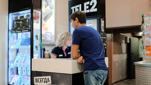 Посетитель у стойки мобильного оператора Tele2