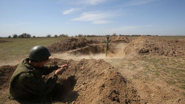 Военнослужащий во время стрельбы из миномета