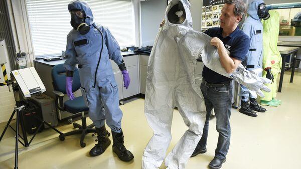 Сотрудник ОЗХО демонстрирует защитный костюм, использовавшийся экспертами во время расследования отравления Сергея Скрипаля в Великобритании