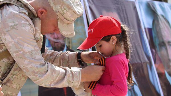 Офицер Российского центра по примирению враждующих сторон вручает Георгиевскую ленту сирийской девочке в Алеппо