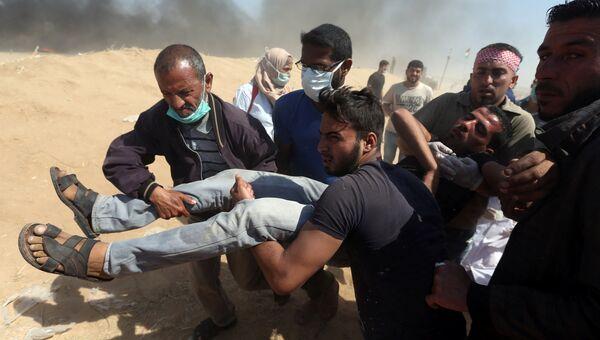 Раненный палестинец во время акции протеста на границе между Израилем и сектором Газа. 15 мая 2018