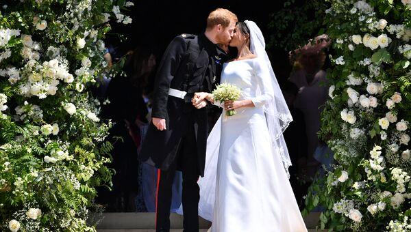 Британский принц Гарри и его жена Меган Маркл на выходе из церкви Святого Георгия в Виндзоре, Англия. 19 мая 2018