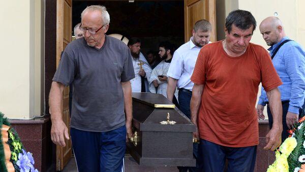 Люди выносят гроб с телом прихожанина Артемия, погибшего при нападении на храм Архангела Михаила в Грозном. 22 мая 2018
