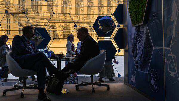 Посетители у павильона АФК Система на Петербургском международном экономическом форуме. 24 мая 2018