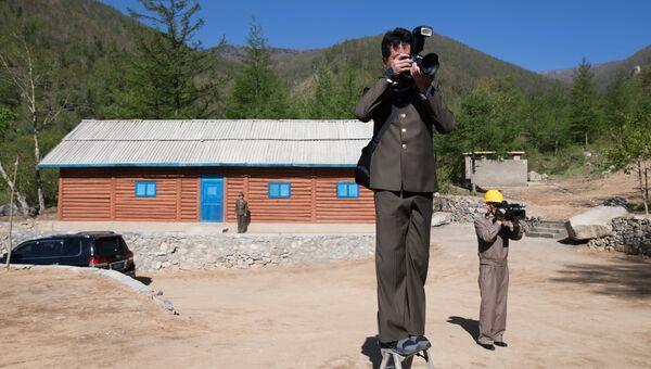 Журналисты из КНДР у здания управления шахтой для ядерных испытаний №2 на ядерном полигоне Пхунгери на севере КНДР