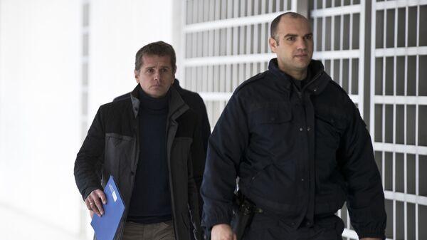 Полицейский сопровождает Александра Винника