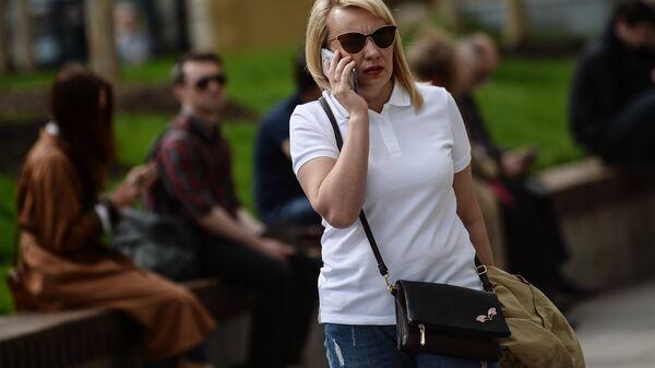 Женщина говорит по телефону на улице Москвы
