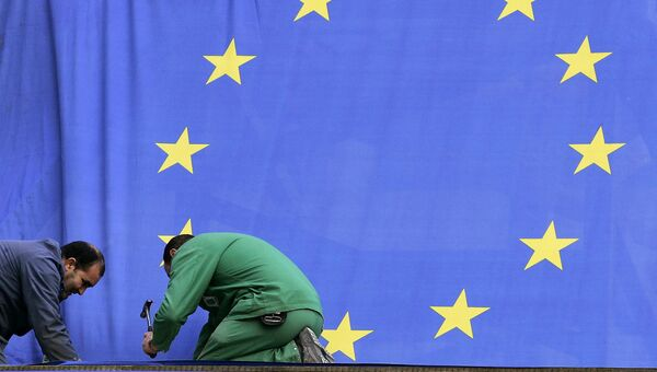 Рабочие прикрепляют флаг Европейского союза возле штаб-квартиры ЕС в Брюсселе