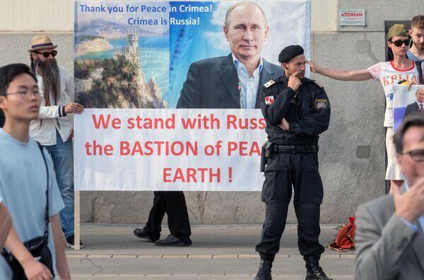 Жители Австрии держат плакат с изображением президента РФ Владимира Путина во время его встречи с федеральным президентом Австрийской Республики Александром Ван дер Белленом во дворце Хофбург в Вене