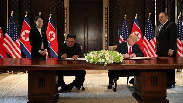 Президент США Дональд Трамп и лидер КНДР Ким Чен Ын Во время подписания документов по итогам встречи в Сингапуре. 12 июня 2018