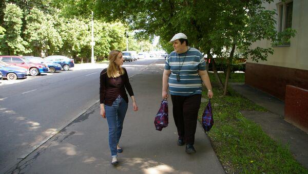 Татьяна и ее подопечный Михаил возвращаются из магазина с покупками.